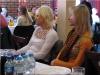 Uczestniczki konferencji siedzą przy stołach oczekując prelekcji