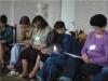 Uczestnicy spotkania siedzący przy ścianie zajęci rozwiązywaniem testów