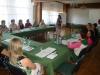 Uczestnicy projektu siedzą przy stole słuchając prelekcji
