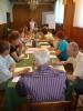 Uczestnicy projektu Aktywni, zintegrowani, silniejsi siedzą przy stole biorąc udział w treningu interpersonalnym